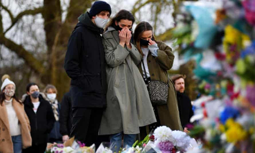 People viewing the floral tributes left at the bandstand on Clapham Common in memory of murdered Sarah Everard.