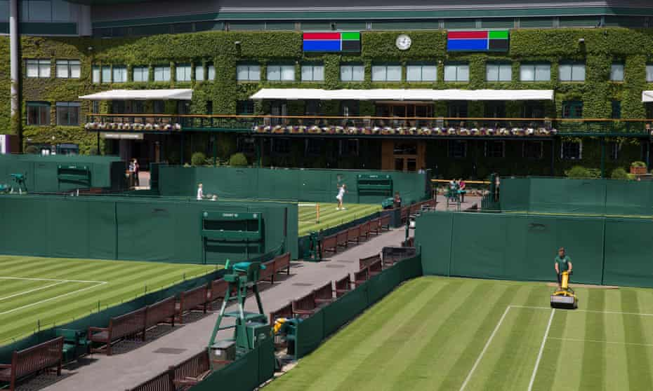 A court is mowed as members play on another of the outside courts at Wimbledon.