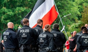 Police officers move towards a protester waving an imperial German flag during a demonstration against lockdown measures in Berlin in May by rightwing extremists