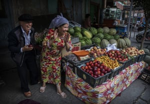 Uyghurs joke with a customer at their fruit stall