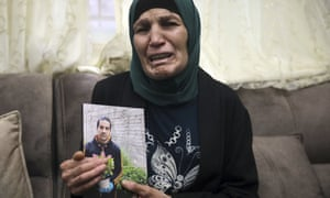 Rana, the mother of Iyad Halak, holds his photo.