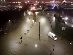 A flooded road in Sheffield. Meadowhall shopping centre, where people were forced to spend the night, is visible in the background.