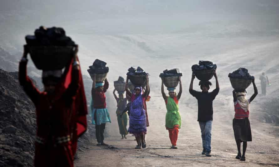 Villagers carry illegally scavenged coal from an open-cast coal mine in Dhanbad, Jharkhand, India