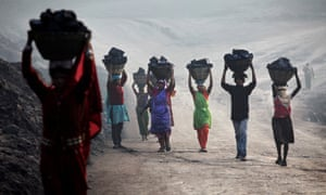 Villagers carry illegally scavenged coal from an open-cast coal mine in Dhanbad