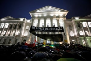 """Protesting students in front of the Parana Federal University in Curitiba. The baner reads """"In defense of education."""""""