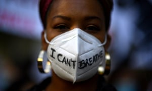 A woman wears a mask reading: I can't breathe.