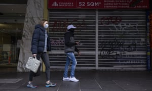 People wearing face masks walk past a closed business along Swanston Street in Melbourne