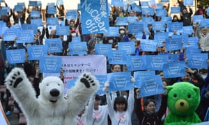 """Environmentalists hold up placards that read """"Climate Action Now!"""" during a rally in Tokyo on Saturday."""