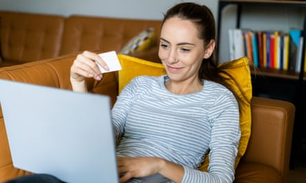 A smiling young woman with a laptop on her knee and a card in her hand