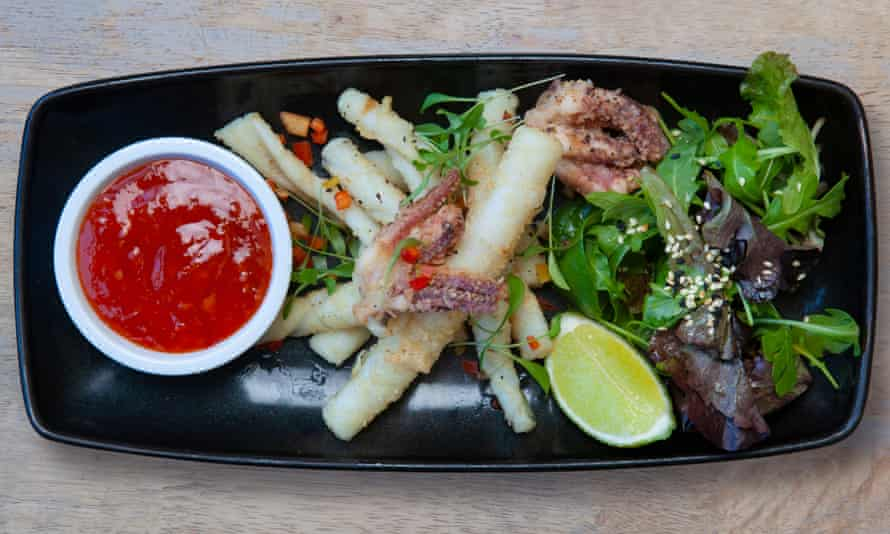 Squid in the middle of a black rectangular platter with a small bowl of red dip on the left and salad on the right