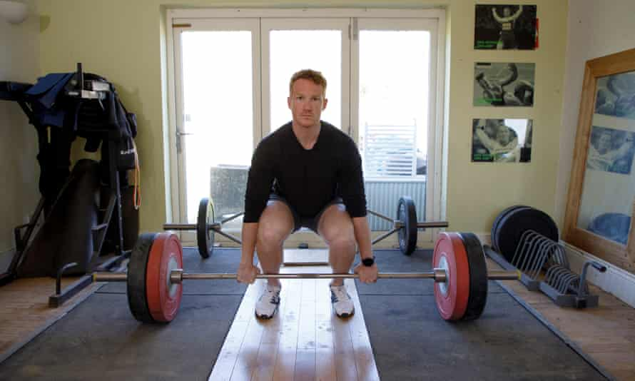 Greg Rutherford lifting weights in the gym at his home.