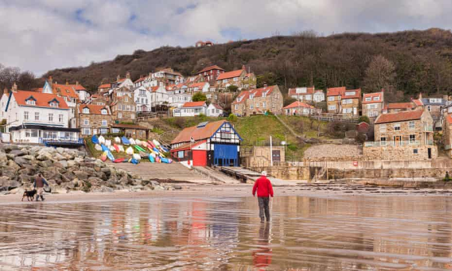 'A jumble of red-roofed cottages opening out on to a wide stretch of beach:' Runswick Bay, North Yorkshire.