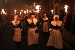 Women carry flaming torches