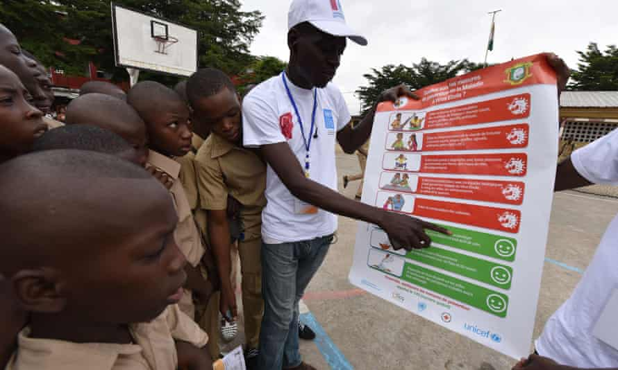 Students look at an ebola prevention poster