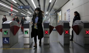 A woman wearing a mask walks out of a ticket barrier in a subway station