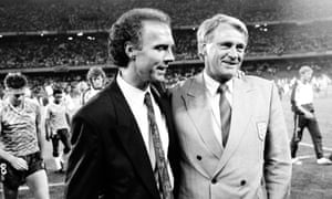Franz Beckenbauer consoles Bobby Robson. Chris Waddle and Paul Parker trudge sadly in the background, wearing their West German souvenir shirts.