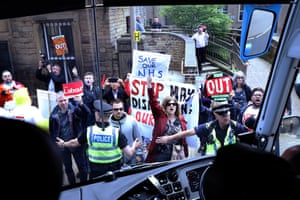 Protesters demonstrate in front of the Conservative party's battle bus, as Theresa May leaves Halifax after launching the manifesto