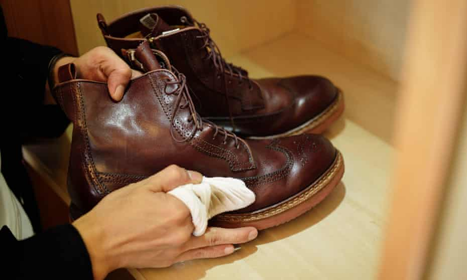 Hands moisturising a pair of brown leather boots with a clean cloth