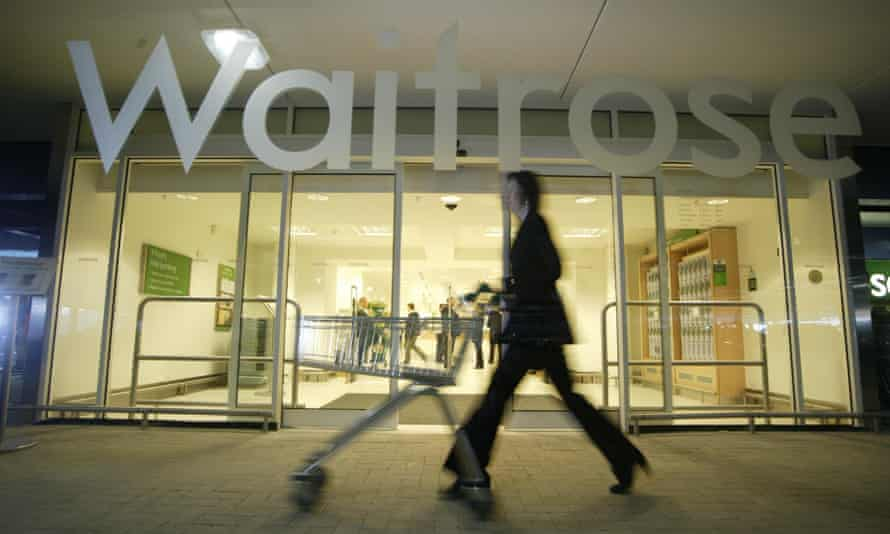 Waitrose store front with woman pushing a trolley past it