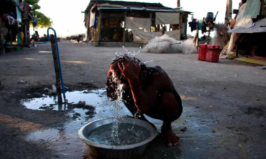 A boy washes himself with water on South Tarawa in Kiribati. Only 55% of people in the Pacific have access to basic drinking water.