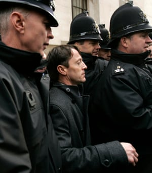 Kieren Fallon is escorted by police officers from the Old Bailey to his taxi
