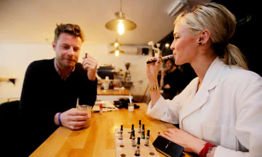 People smoking e-cigarettes in a coffee shop in London.