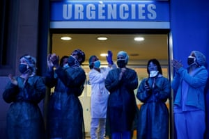 Health workers react as neighbours of the Dos de Mayo hospital take part in the daily nationwide applause in Barcelona.
