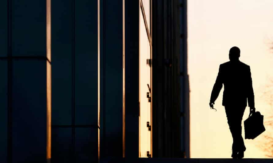 A silhouette of a man in a suit outside a building