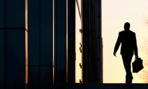 A male worker arrivers at his office in the Canary Wharf district of London