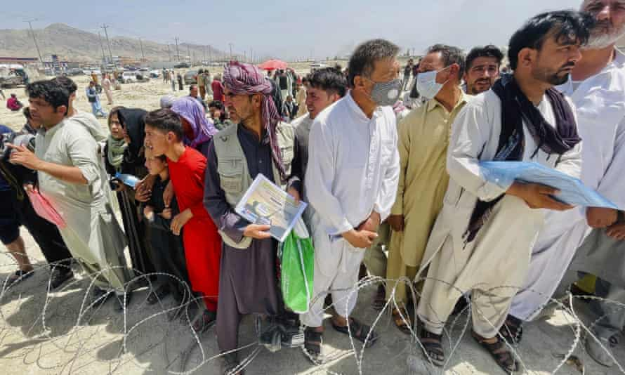 A man holds a certificate acknowledging his work for Americans as people gather outside Kabul international airport on Tuesday