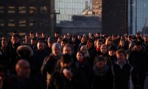 Commuters walk across London Bridge