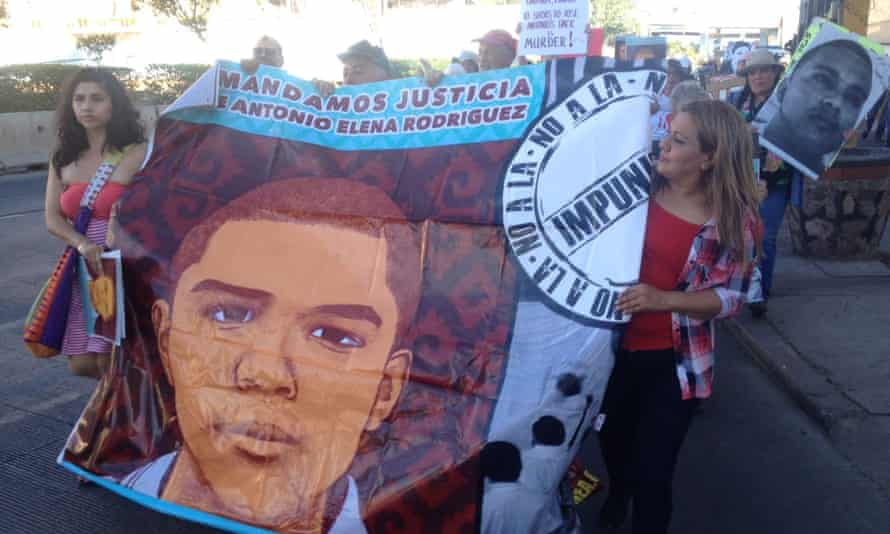 Araceli Rodríguez, the mother of José Antonio Elena Rodríguez holds a banner with her son's image as part of a march demanding a retrial of the agent who shot her son.