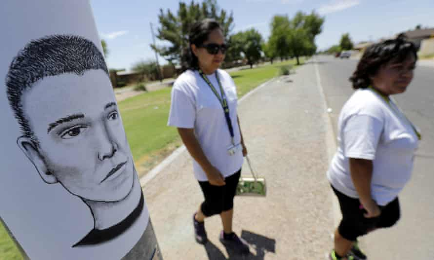 Neighborhood patrol officers walk the Maryvale section of Phoenix to hand out an artist rendering of a suspected serial killer, as shown on the light pole.