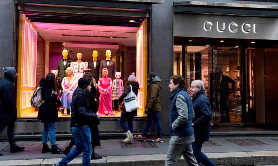 People walk past the window of Gucci on via Montenapoleone in Milan.