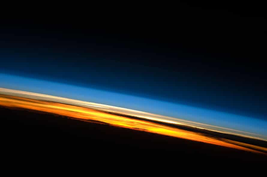 Sunset over the Indian Ocean. Above the darkened surface of Earth, a brilliant sequence of colors roughly denotes several layers of the atmosphere. Deep oranges and yellows are visible in the troposphere that extends from Earth's surface to 6-20 kilometers high. The pink to white region above the clouds appears to be the stratosphere; this atmospheric layer generally has little or no clouds and extends up to approximately 50 kilometers above Earth's surface. Above the stratosphere blue layers mark the upper atmosphere as it gradually fades into the blackness of outer space.