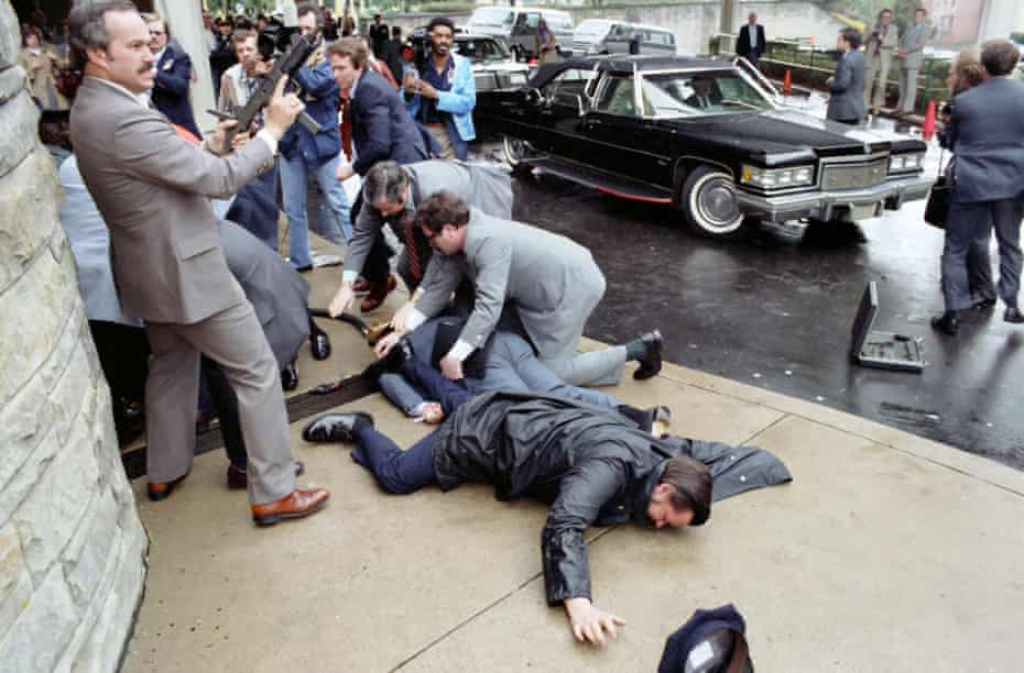 White House Press Secretary James Brady and police officer Thomas Delahanty lie wounded outside the Washington Hilton after the assassination attempt on Ronald Reagan on 30 March 1981.