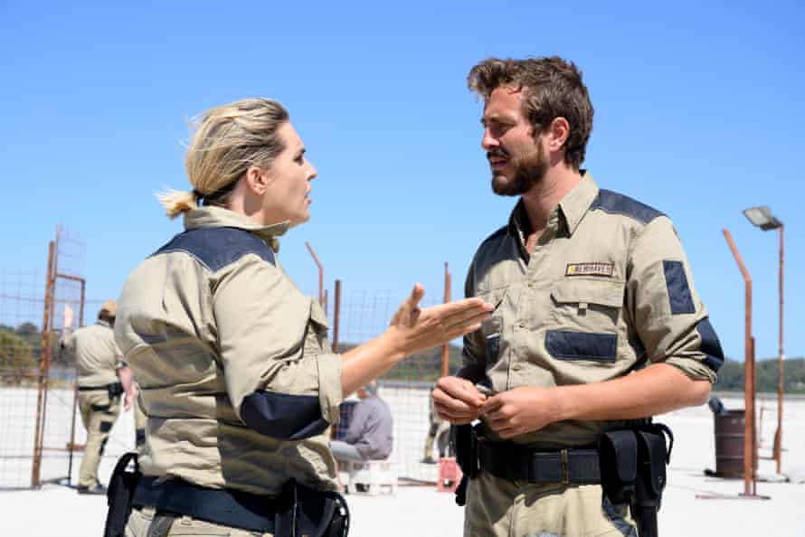 A man and a woman stand in the desert arguing