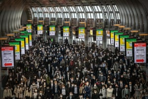 Commuters, mostly wearing face masks, walk through Shinagawa train station in Tokyo on Wednesday.