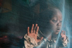 A child in Nairobi plays under an insecticide-treated mosquito net.