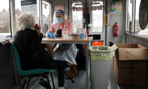 A healthcare worker helps a woman to take her swab sample, at a minibus that was converted into a Covid-19 mobile test centre in Walsall, England.