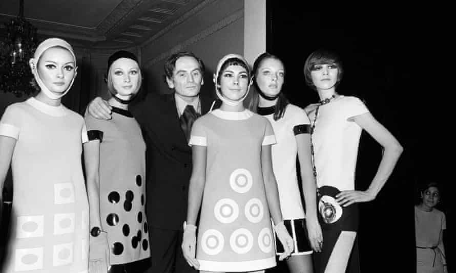 Pierre Cardin flanked by models after 1967 show in Paris.