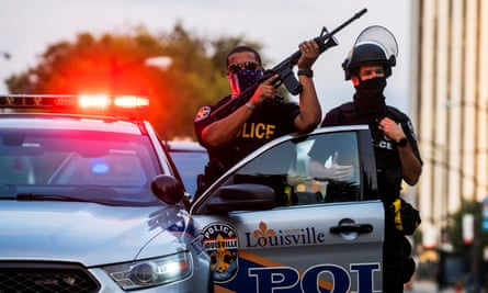 Police officers stand guard as demonstrators march during a peaceful protest in Louisville, Kentucky on 26 September.
