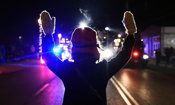 A protester holds her hands up in front of a police car in Ferguson, Missouri