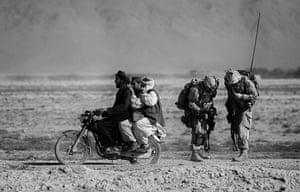Salavat, Afghanistan, September 2010. Afghan men on a motorcycle overtake Canadian soldiers during a patrol in Panjwaii district