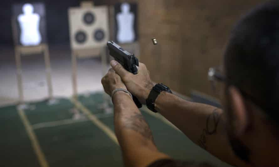 A pistol is fired during a practice session at the Calibre 12 gun club in Sao Goncalo, Brazil