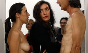 A visitor squeezes past a naked women and man as part of the Imponderabilia experience in Basel