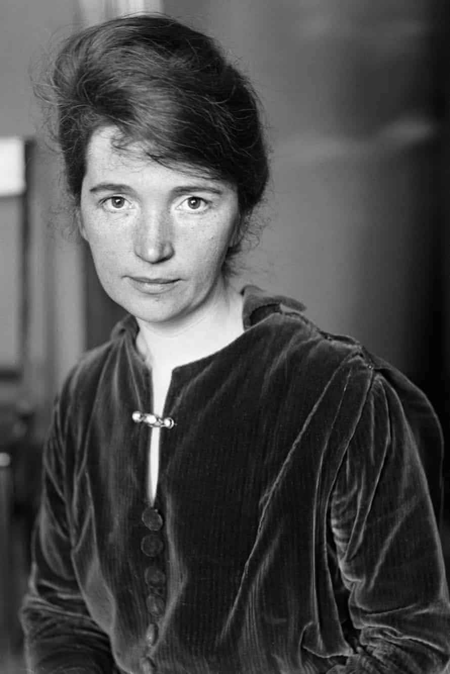 A young woman looks directly at the camera in this black and white photo; her hair is piled into a high french roll, and she is wearing a dark velvet tunic with a barrette-style brooch pinned across the front vent.