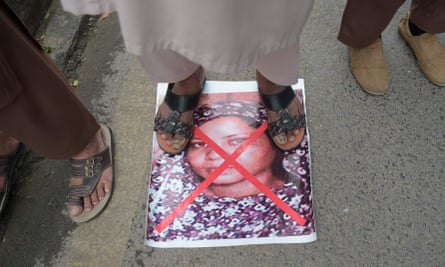 A Pakistani supporter of hardline religious party the ASWJ stands on an image of Asia Bibi during a protest rally on 2 November