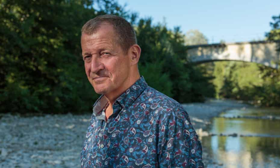 Alastair Campbell standing by a stream in the sunshine