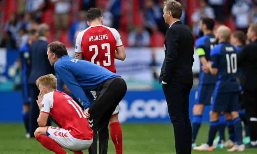 Denmark's coach, Kasper Hjulmand (right), and players look on while Christian Eriksen receives emergency medical treatment on Saturday.